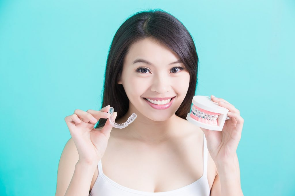 Woman holds Invisalign aligner and prosthetic teeth with metal braces to show the differences between the two