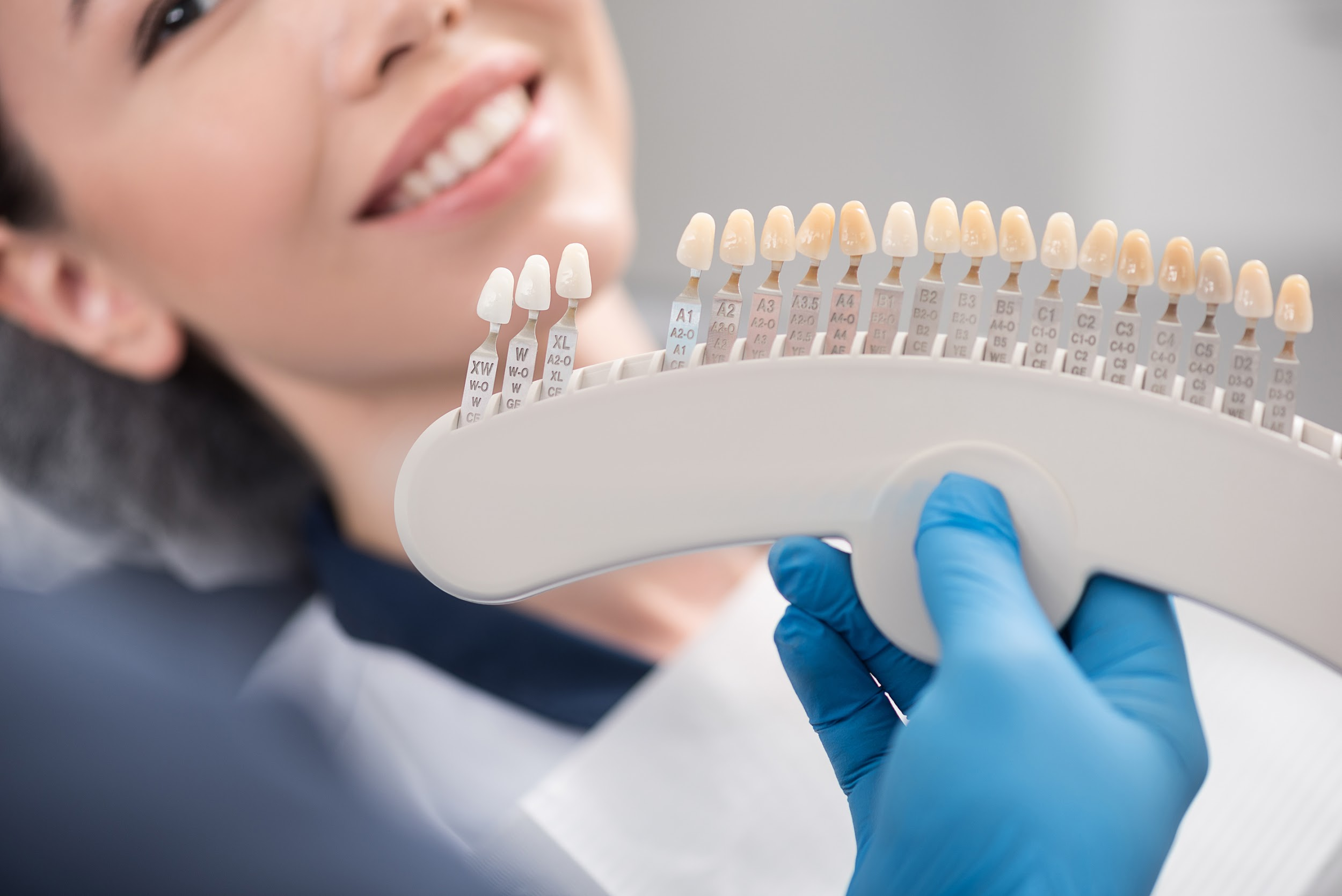 Dentist color-matches dental implant crown with existing teeth