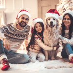 Family wears Christmas hats and sweaters and smiles at camera
